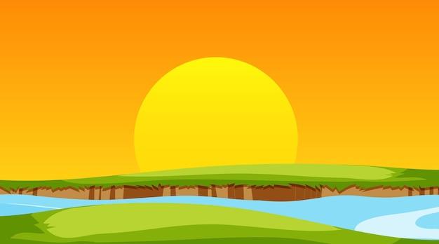 Leeg weidelandschap en rivier bij zonsondergangtijdscène