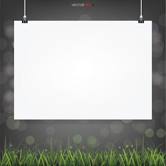 Leeg wit posterpapier op groen gebiedsgebied met lichte bluured bokeh op donkere achtergrond