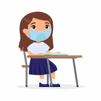 Leerling bij les met beschermend masker op haar gezicht. schoolmeisje zit in een schoolklas aan haar bureau