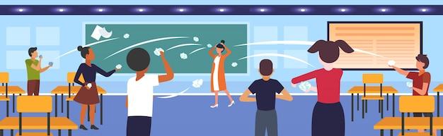 Leerlingen demonstreren slecht gedrag gooien papieren spottende en plagen vrouwelijke leraar tijdens les pesten openbare afkeuring concept school klas interieur horizontaal