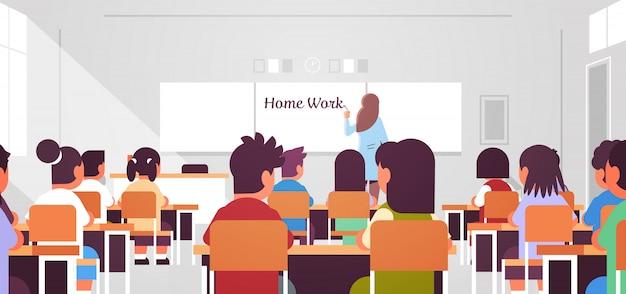 Leerlingen groep zitten en kijken naar vrouwelijke leraar schrijven thuiswerk op schoolbord in de klas tijdens les onderwijs concept moderne klas kamer interieur