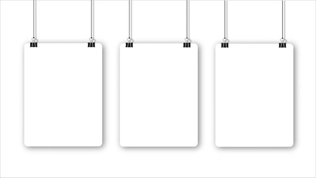 Lege poster die aan een bindmiddel hangt, een vel wit papier hangt aan een touw met clips