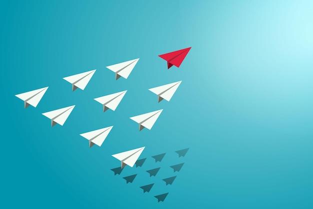 Leiding van rode papieren vliegtuigjes leidt een groep witte vliegtuigen
