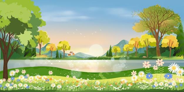 Lente seizoen in dorp met meer, berg, groene weide, oranje en blauwe lucht in de avond, landschap van het platteland.