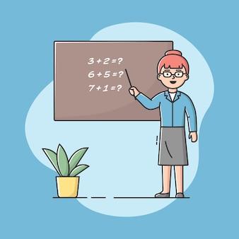 Leraar in uniform op het bord. professionele werknemer. zelfverzekerde vrouw in klaslokaal.