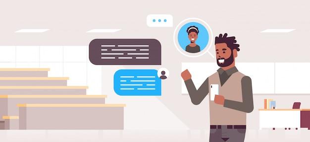 Leraar met behulp van smartphone sociaal netwerk praatjebel communicatieconcept