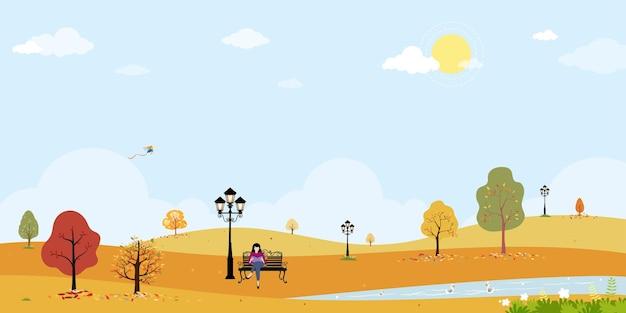 Leuk herfstparklandschap in openbaar park met jonge vrouwen die op een bankje zitten