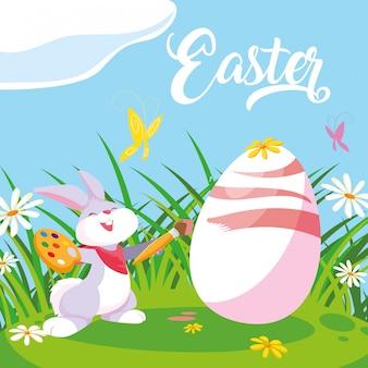 Leuk konijn het schilderen ei van pasen in tuin