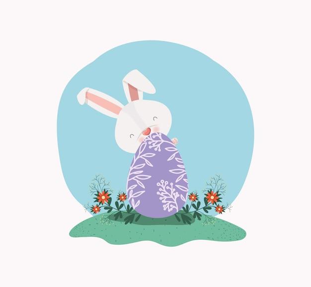 Leuk konijn met geschilderd ei en bloemen in de tuin