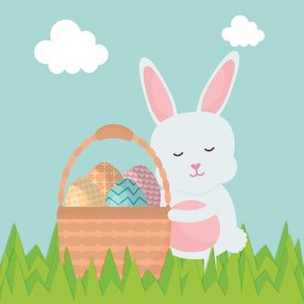 Leuk konijn met paaseieren die in mand worden geschilderd