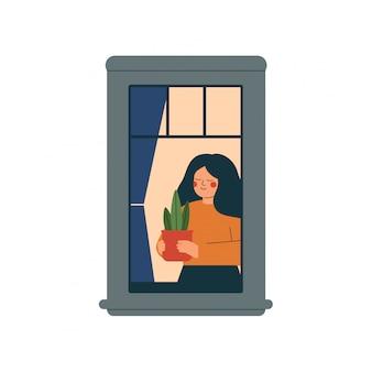 Leuk meisje dat een installatie draagt aan het zonlicht. jonge vrouw aanplant potplant in de buurt van het open raam.