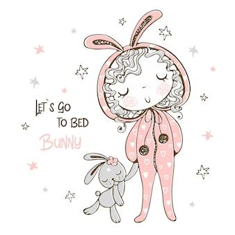 Leuk meisje in pyjama in de vorm van een konijn gaat slapen met speelgoed.