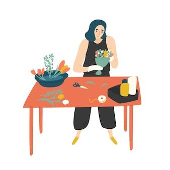 Leuke gelukkige vrouw die aan tafel staat en een boeket maakt