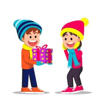 Leuke jongen geeft een cadeau aan een klein meisje in de winter
