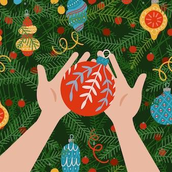 Leuke kerstavondscène het uitzicht vanuit de ogen twee handen die de kerstbal vasthouden en kerstversiering...