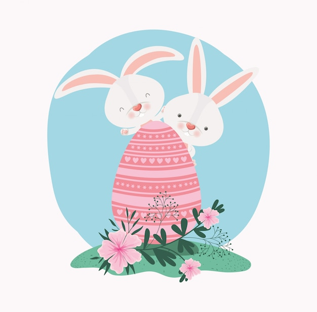 Leuke konijnen met geschilderd ei en bloemen in de tuin