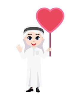Leuke mooie arabische jongen jongen karakter staan ?? en zwaaien en vasthouden aan de lege banner van de hartvorm met traditionele kleding geïsoleerd