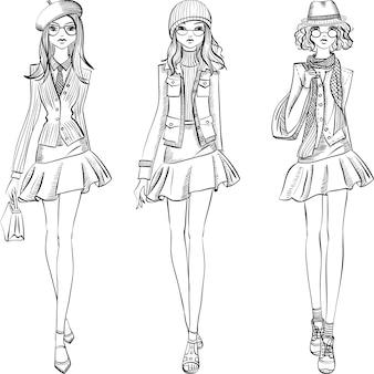 Leuke mooie modieuze hipster meisjes in jassen, rokken en petten met tassen.