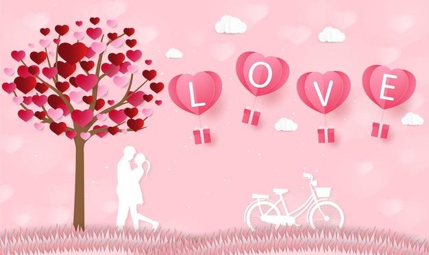 Liefde en valentijnsdag liefhebbers staan in de weilanden en een papieren hartvormige ballon zweeft