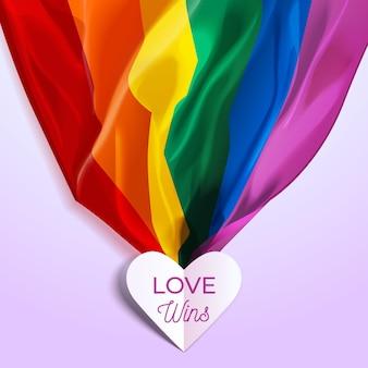 Liefde wint belettering in een hart en trots regenboogvlag