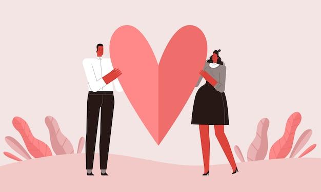 Liefhebbers van man en vrouw houden een hart vast als een symbool van liefde. geïsoleerd op witte achtergrond.