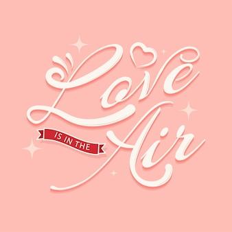 Love is in the air lettertype met hart op pastel rode achtergrond.