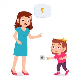 Mam waarschuwt haar kind meisje dat stopcontact speelt