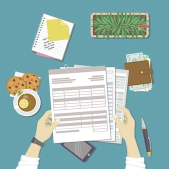 Man aan het werk met documenten. menselijke handen houden de rekeningen, loonlijst, belastingformulier.