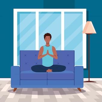 Man afro mediteren in de woonkamer, zittend in bank