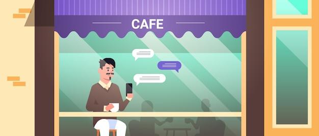 Man bezoeker zittend aan tafel met behulp van chatten mobiele app op smartphone sociaal netwerk chat bubble communicatie