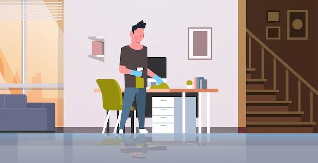 Man computer tafel schoonmaken met stofdoek man afvegen werkplek bureau huishoudelijk concept moderne woonkamer interieur mannelijke stripfiguur