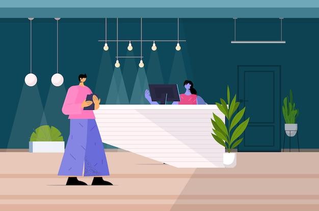 Man die bij de receptie staat en met de receptioniste in hotel of kantoor in volle lengte praat