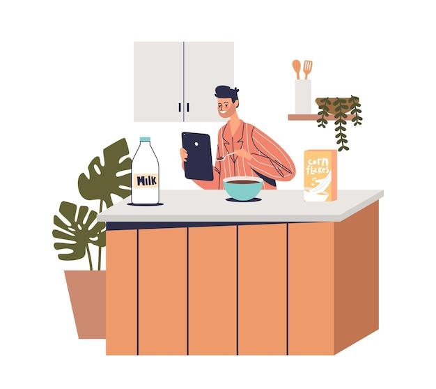 Man die digitale tablet gebruikt om op internet te surfen en video te kijken tijdens het ontbijt in de keuken