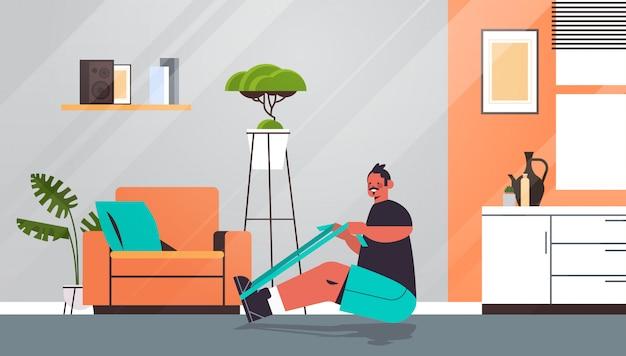 Man doen oefeningen met weerstand band thuis man met training cardio fitness training gezonde levensstijl sport concept woonkamer interieur volledige lengte illustratie