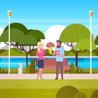 Man geeft meisje cadeau en boeket over groen park gefeliciteerd voor internationale vrouwendag 8 maart vakantie