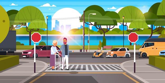 Man help senior vrouw met wandelstok oversteken van straat