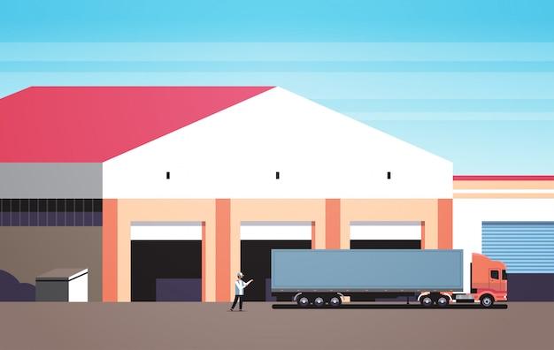 Man helpt grote vrachtwagen rijden in magazijn parkeren