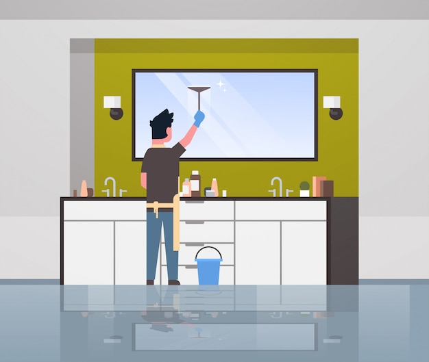 Man in handschoenen en schort schoonmaken spiegel met zuigmond man huishoudelijk werk concept doen moderne badkamer interieur achteraanzicht mannelijke karakter