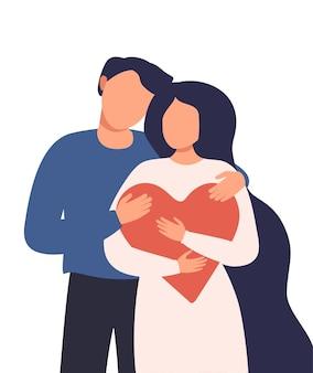 Man knuffelt een vrouw die een groot rood hart vasthoudt