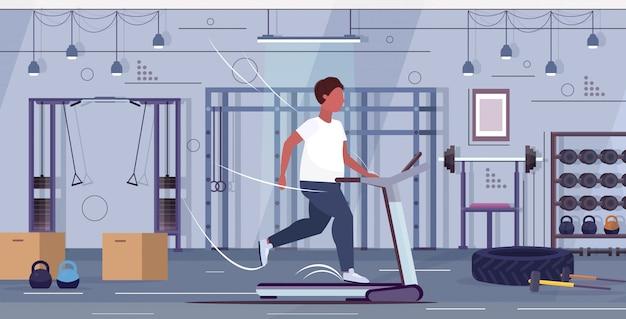 Man loopt op loopband overgewicht man sport activiteit cardio training training gewichtsverlies concept moderne sportschool interieur plat volledige lengte horizontaal