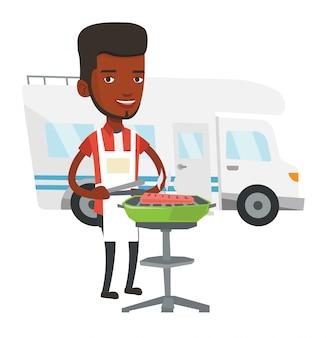Man met barbecue voor camper.