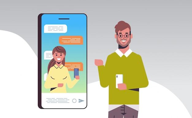 Man met behulp van smartphone online conferentie video-oproep met vrouwelijke collega sociale netwerk communicatieconcept