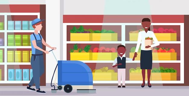 Man met professionele wasmachine mannelijke schonere supermarkt conciërge in uniform schoonmaak service vloer zorg concept moderne kruidenier winkel binnenlandse platte volledige lengte horizontaal