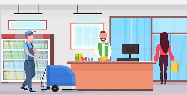 Man met professionele wasmachine schonere supermarkt conciërge in uniform schoonmaak service concept moderne winkel teller bureau kruidenier binnenlandse platte volledige lengte horizontaal