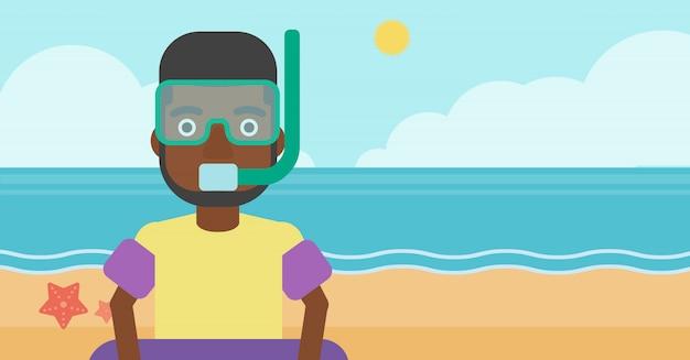 Man met snorkeluitrusting op het strand.