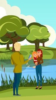 Man neemt foto vrouw met meisje op oever van de rivier