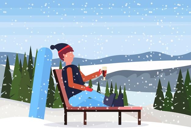 Man ontspannen op lounge stoel na snowboarden in skigebied