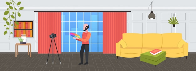Man ontwerper bedrijf gekleurde palet monsters blogger opname online video met digitale camera op statief sociaal netwerk blogging concept modern design studio interieur volledige lengte horizontaal