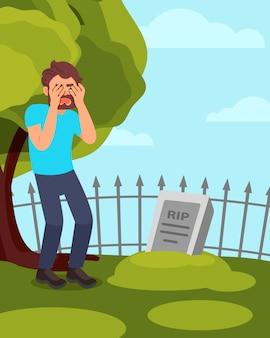 Man permanent in de buurt van grafsteen en huilen. rouwende kerel die graf bezoekt. groene boom, hek en blauwe stal op achtergrond.