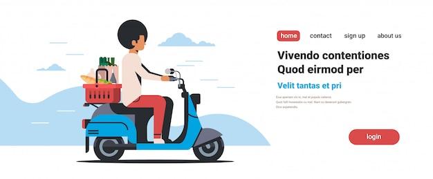 Man rijden scooter met winkelmandje vol met kruidenierswaren verse levensmiddelen levering